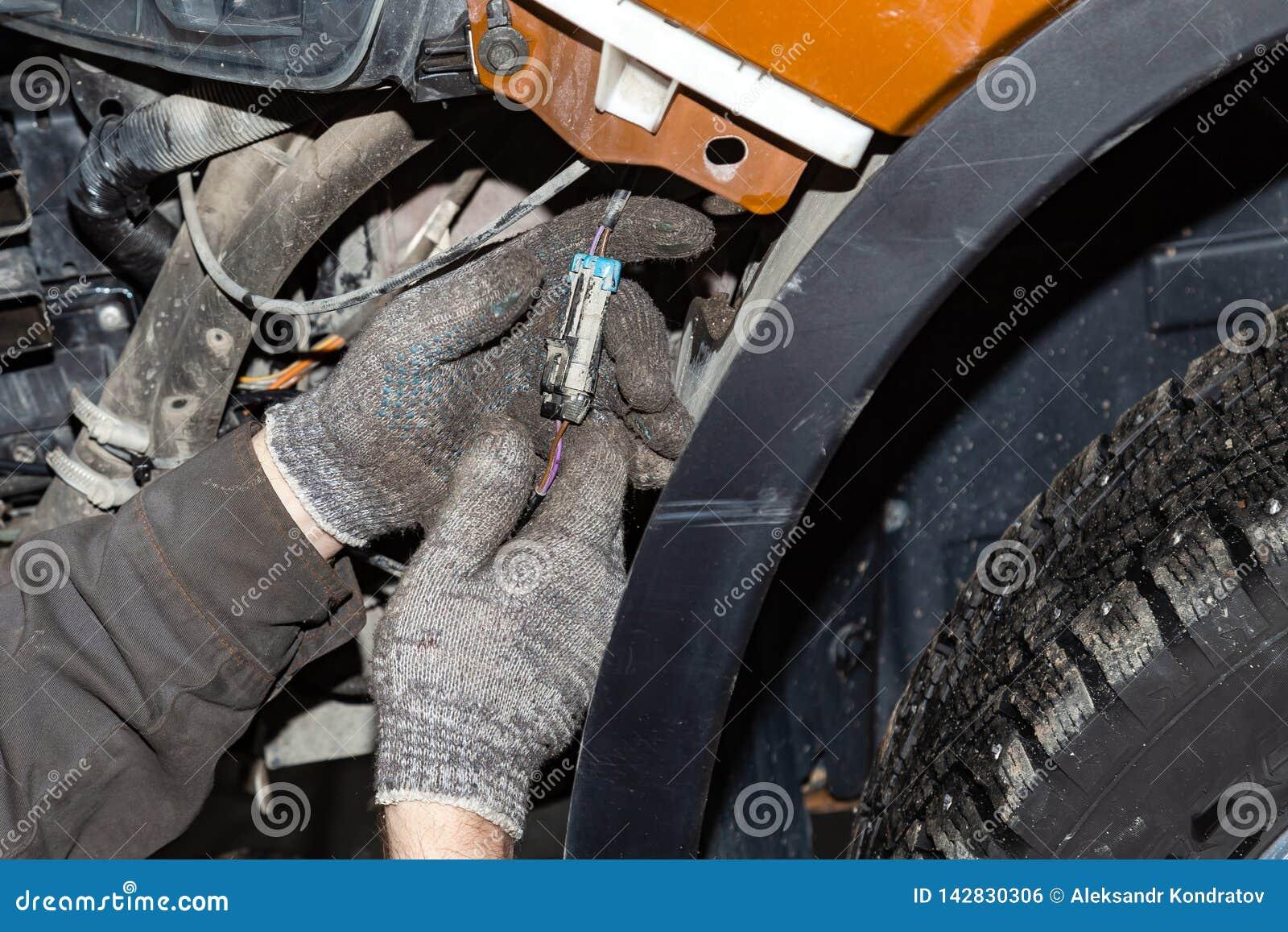 Close-up nas mãos do mestre nas luvas protetoras que conectam o conector com os fios no circuito elétrico do