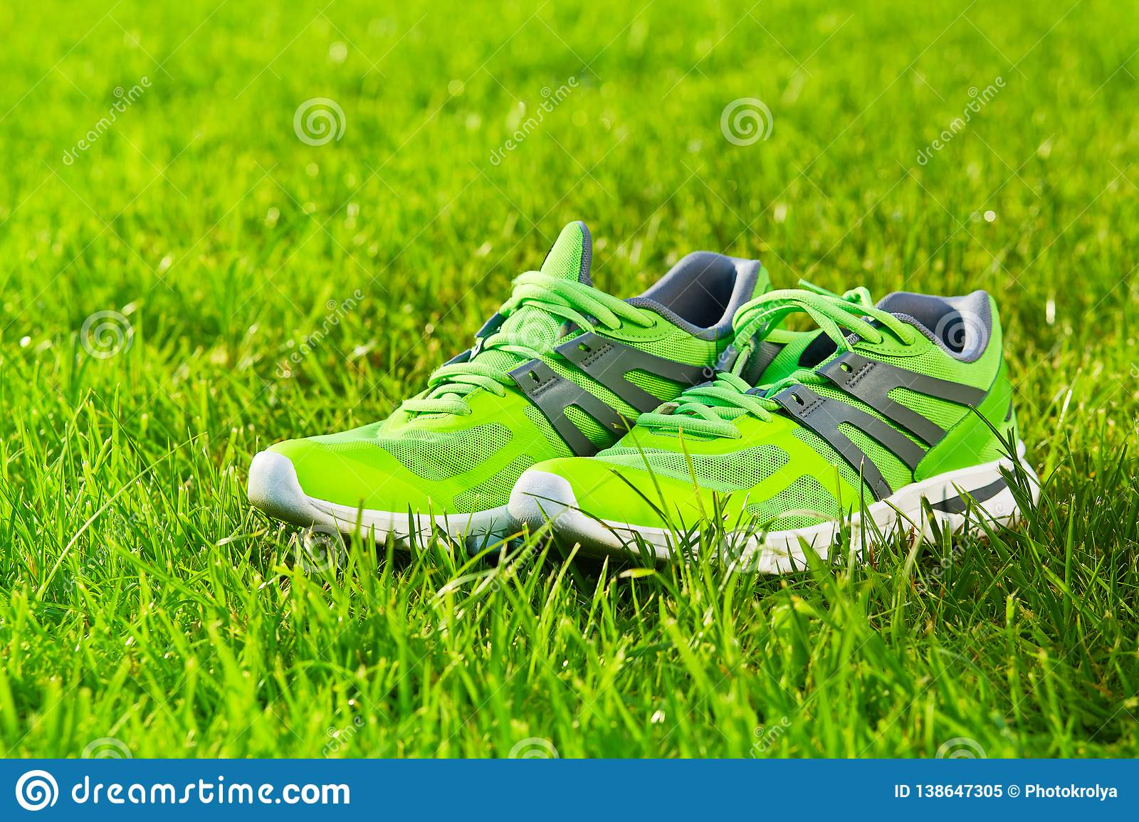 Close up new pairs of green running shoes / sneaker shoes on green grass field in the park
