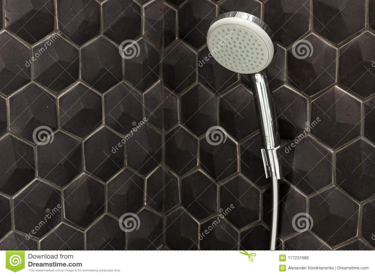 Close up of new rain shower head in the bathroom against a background of black tiles.