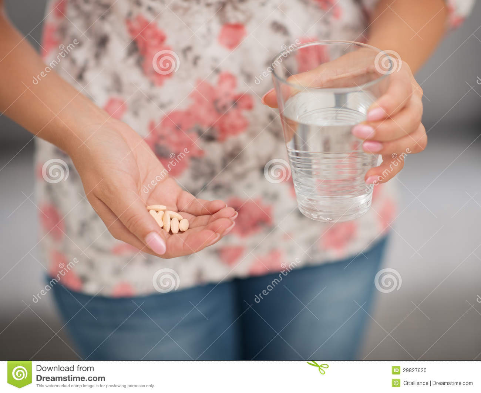 Close up no comprimido e vidro da água à disposição da menina