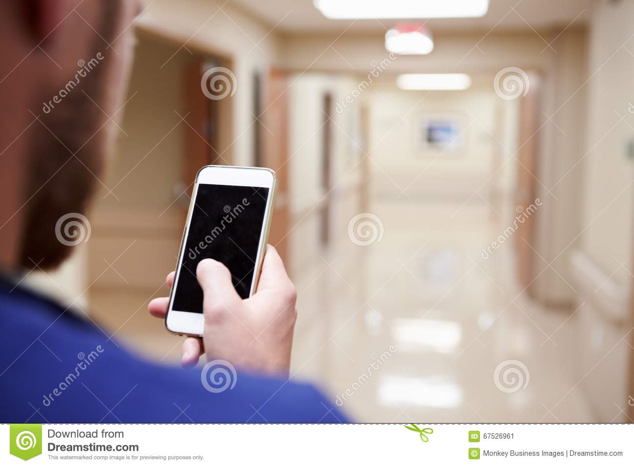 Close Up Of Nurse With Cellphone In Hospital Corridor