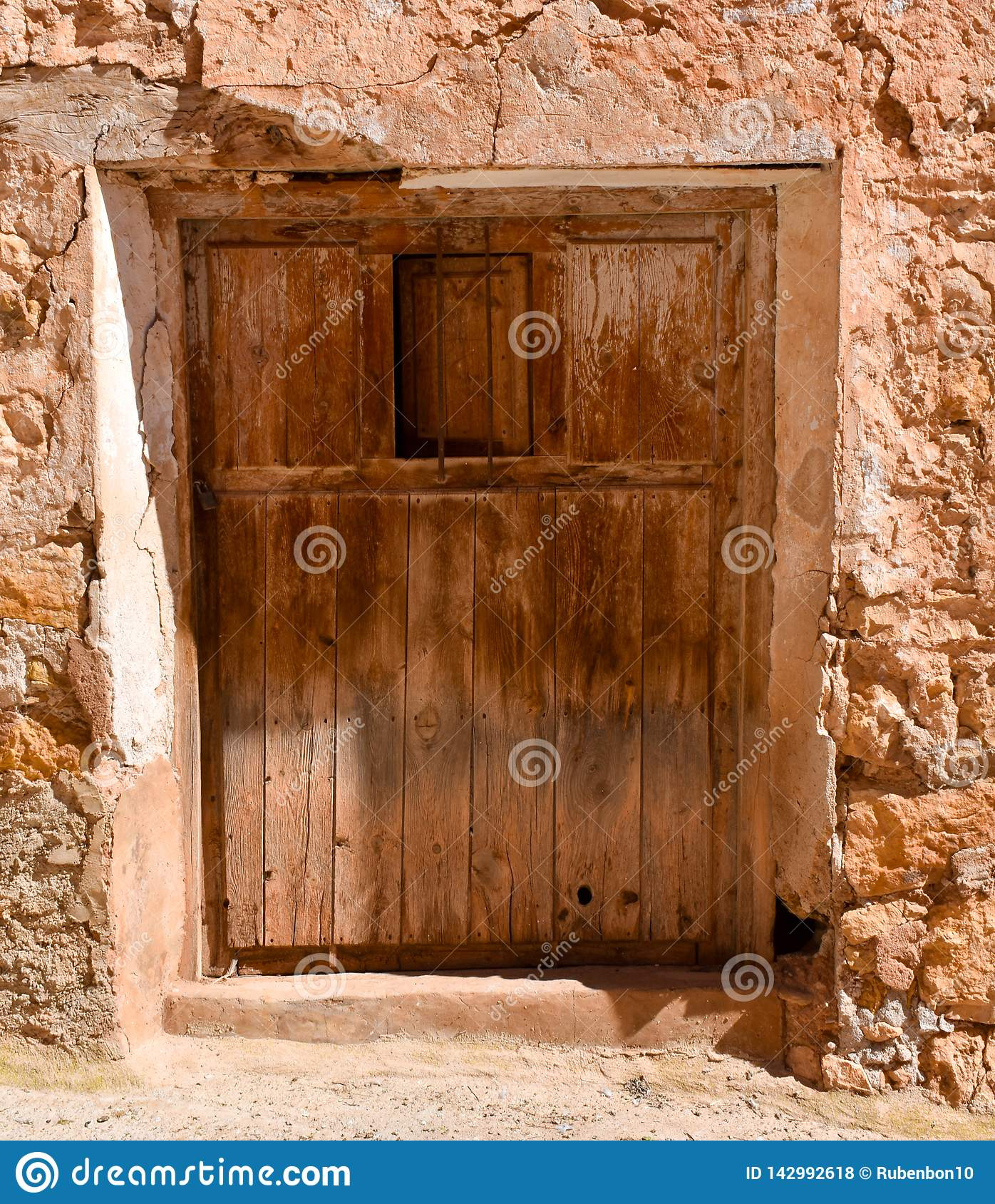 close up of an old wooden closed door with an opened small window in a wall of concrete, mud and stone in a closed abandoned house