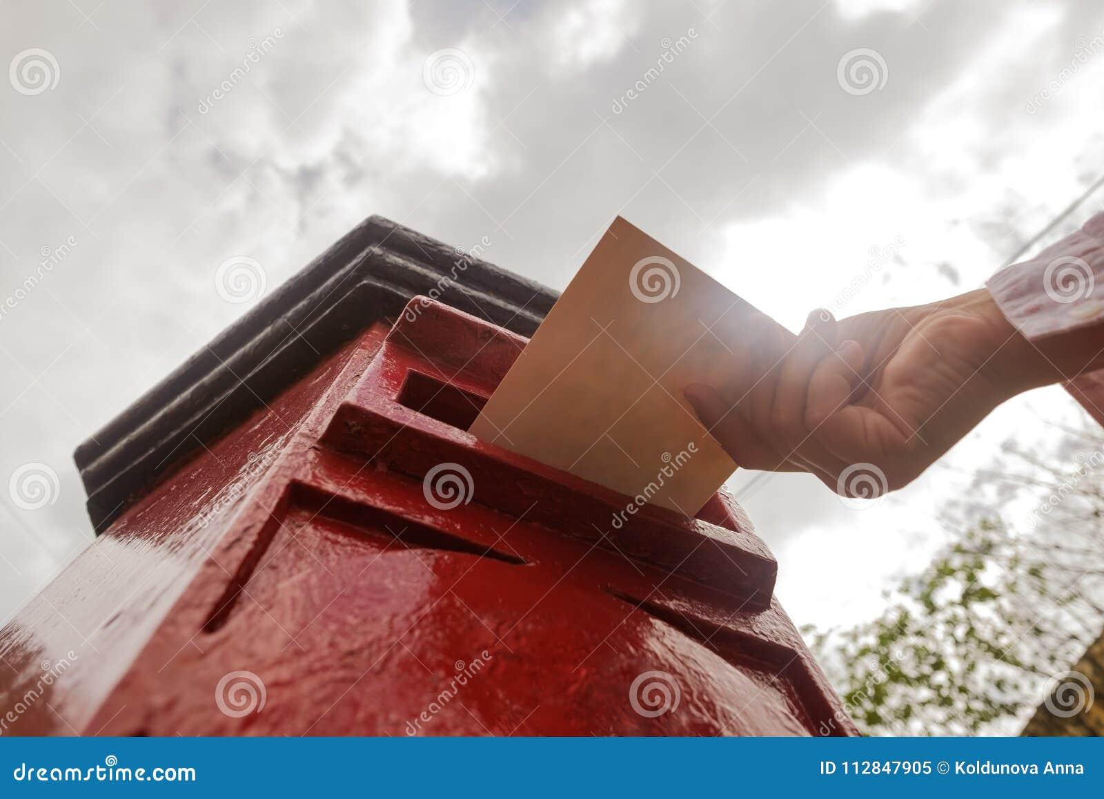Close-up op een mannelijke hand die een brief in een gedenkwaardig vakje zetten Concept uitstekend type van mededeling