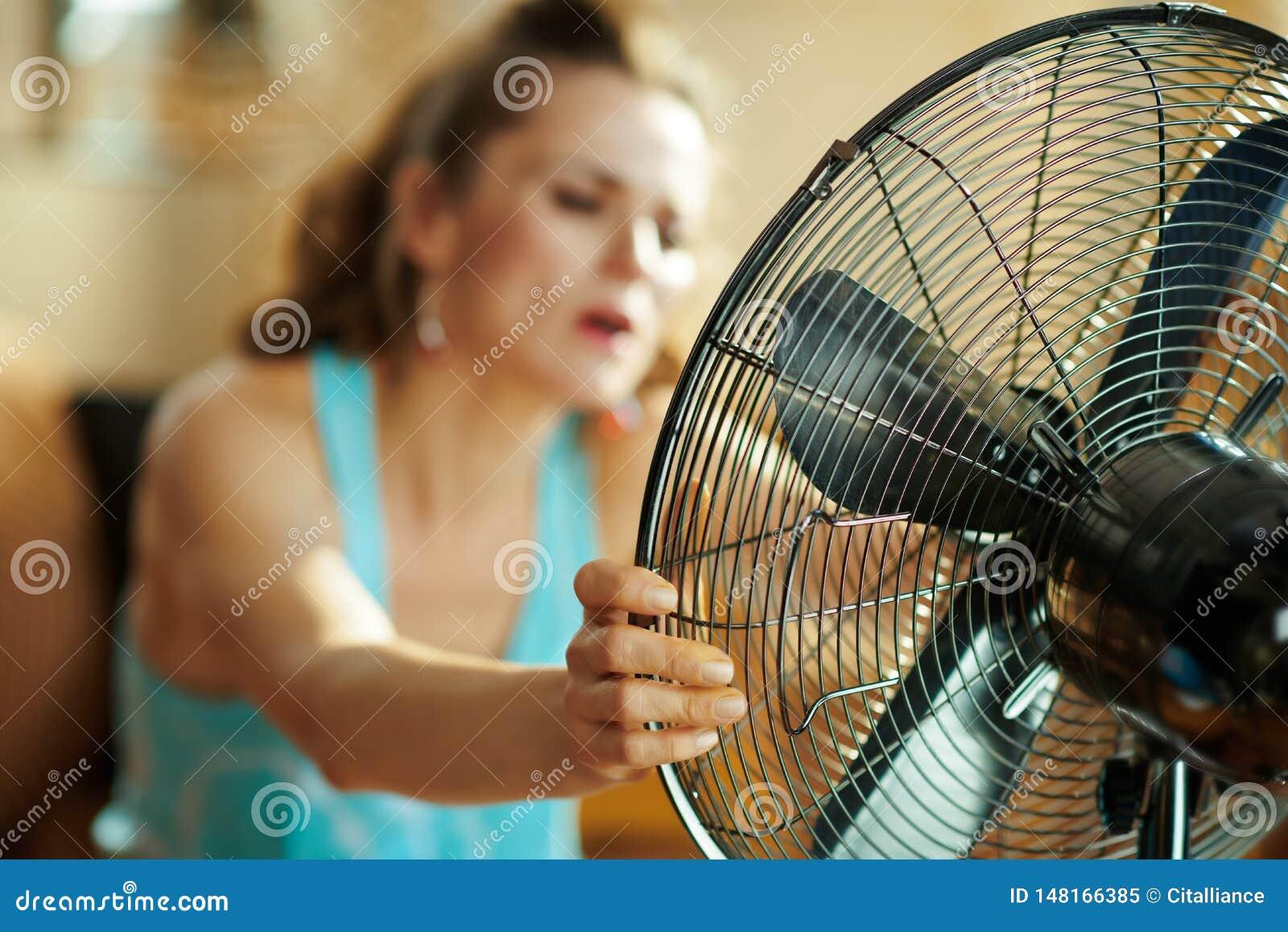 Close-up op huisvrouw die ventilator met behulp van die aan de zomerhitte lijden