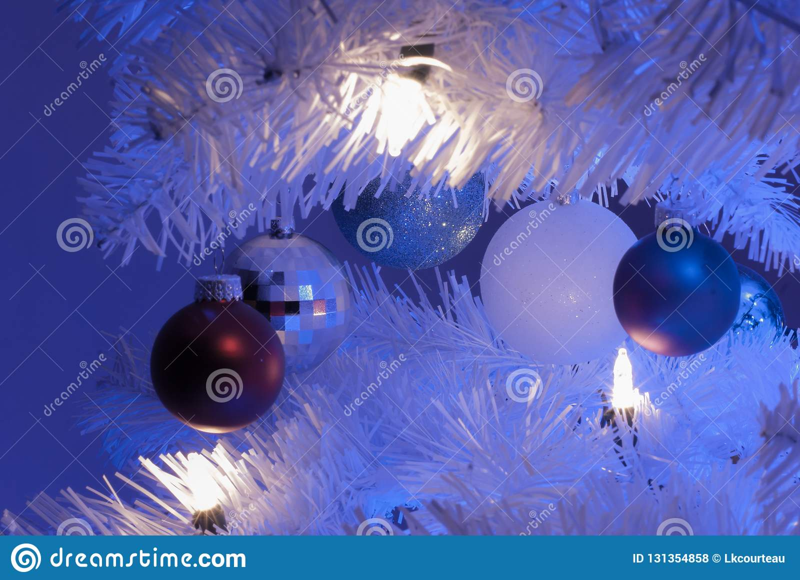 White Christmas Tree With Blue Lights.Close Up Of 5 Ornaments In White Christmas Tree With White