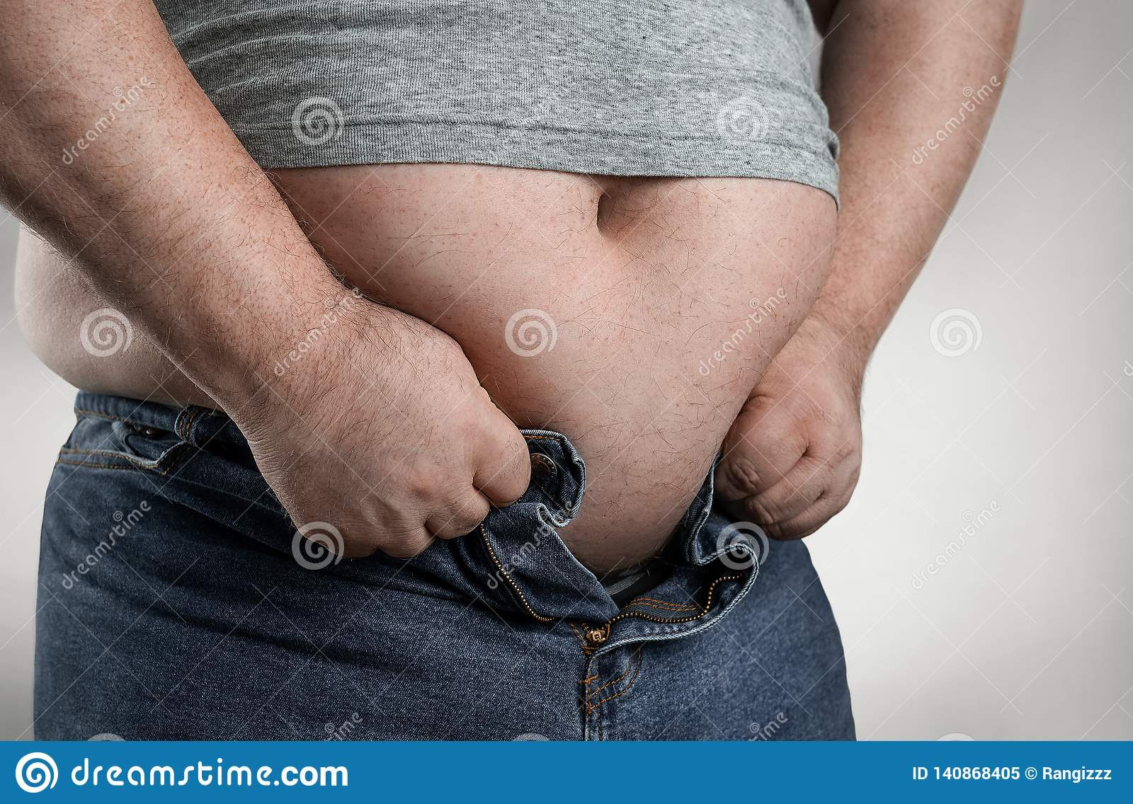 Close up of overweight man trying to wear small jeans