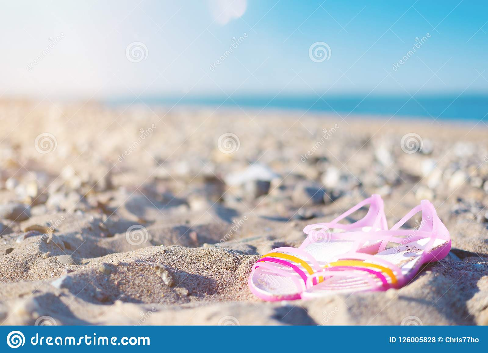 1c403262d Low angle view close-up of pair of shoes on empty beach on clear sunny  summer day