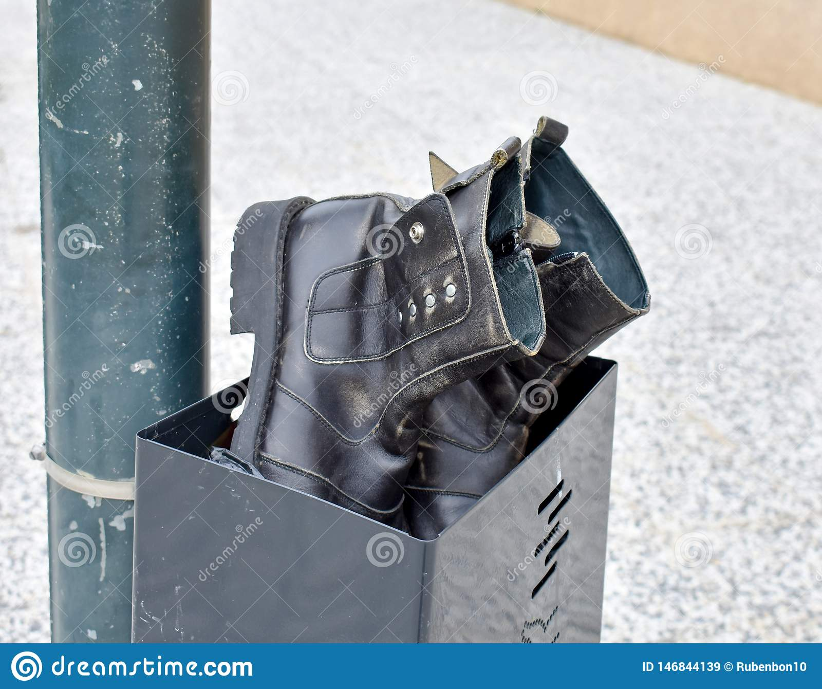 a pair of used black boots made in black leather abandoned in a black bin. Boots and bin at a post in the sidewalk of the street.