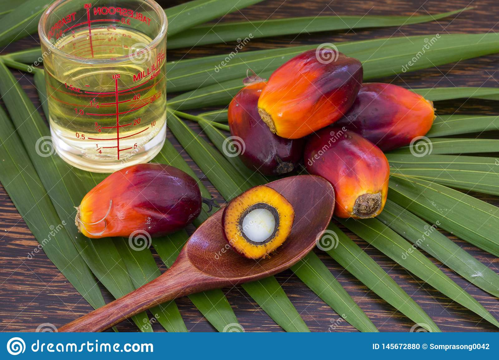 Close up of Palm Oil fruits with cooking oil and palm leaf on a wooden background
