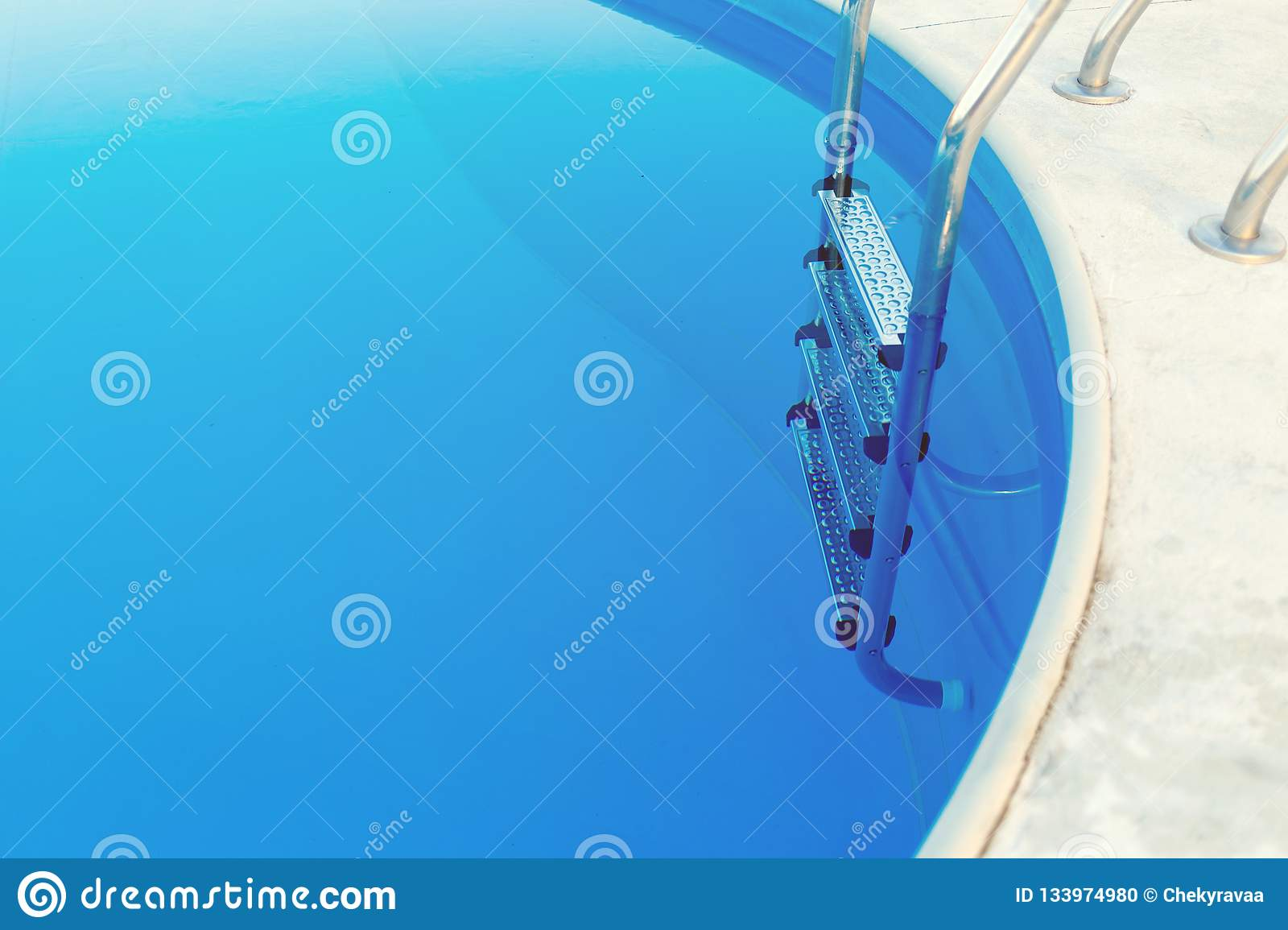 Close-up of a part of swimming pool with a stainless steel ladder and blue water on sunset. Summer vacation, holidays, relax