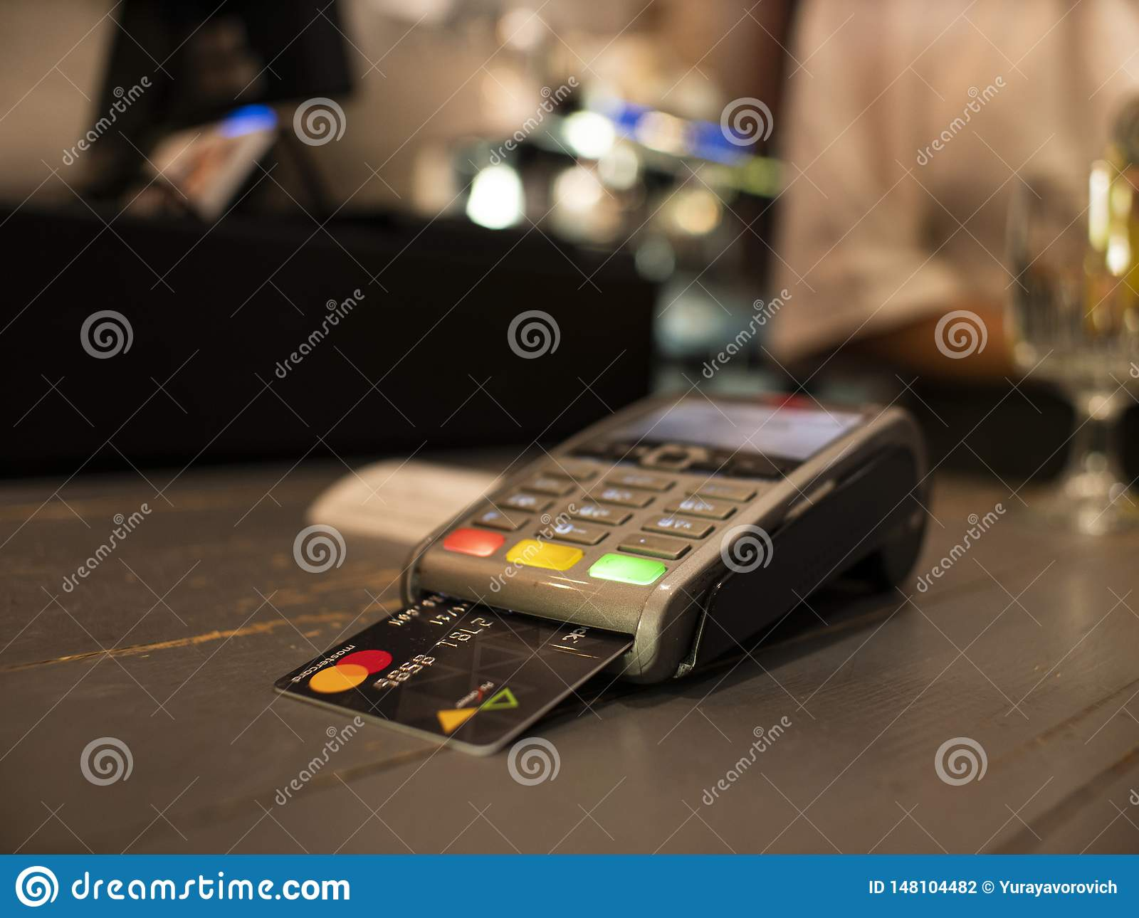 Close up payment machine on the table for paying bill by at table. wireless pos terminal with card