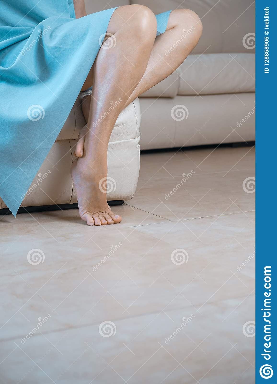 5dc46e0dd0e Cropped side view portrait of woman`s perfect thin slim legs and blue mint  dress. Lady sitting on beige chair having ideal legs. Feet care tights  pedicure ...