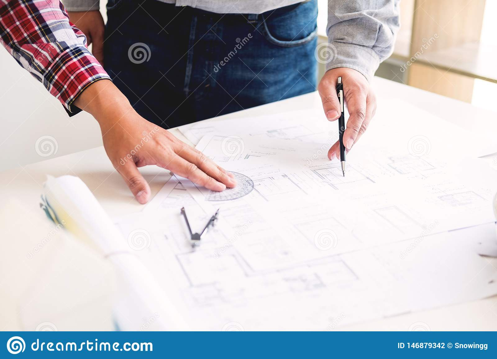 Close-up Of Person s engineer Hand Drawing Plan On Blue Print with architect equipment, Architects discussing at the table, team