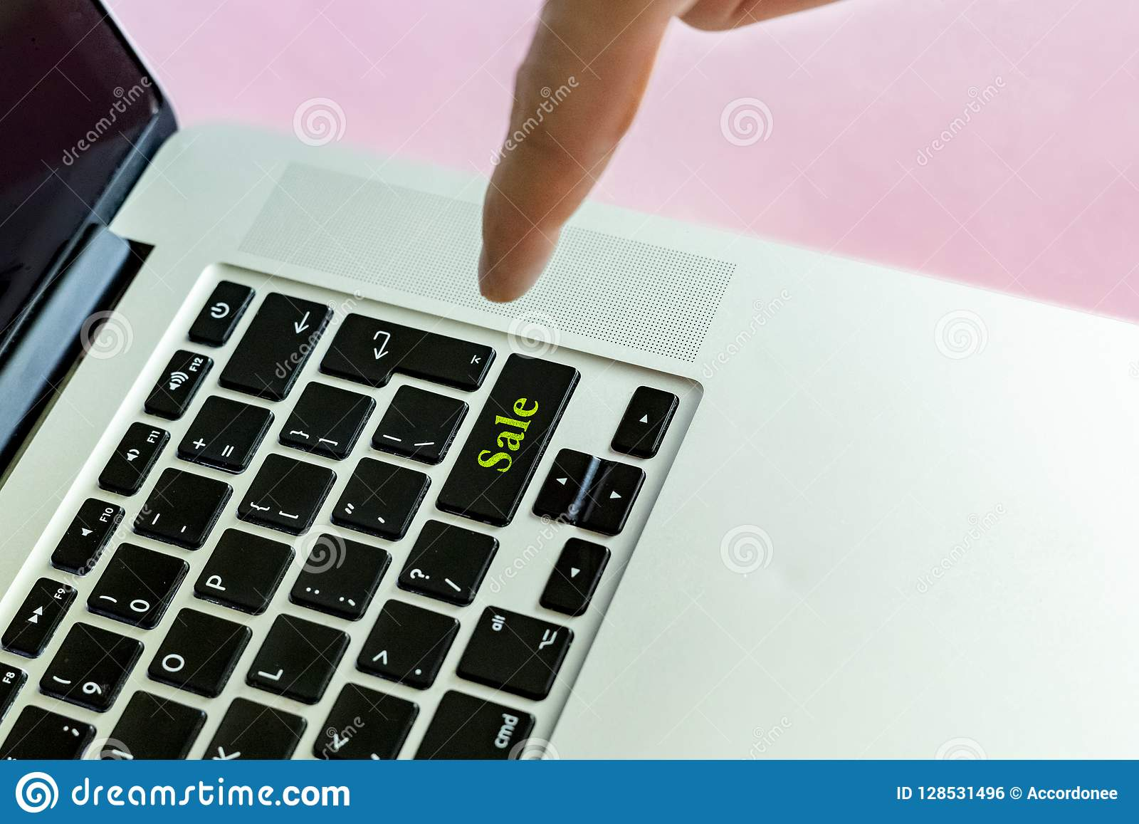 Close up person`s hand finger pushing the `sale` text on a button of laptop keyboard isolated concept v