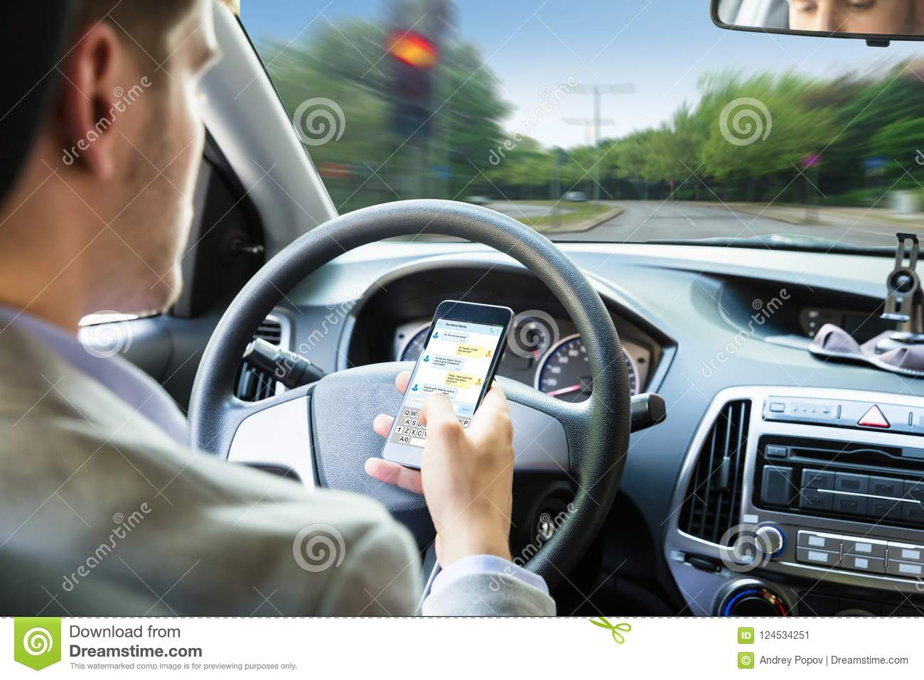 Person Sending Text Message By Mobile Phone While Driving Car