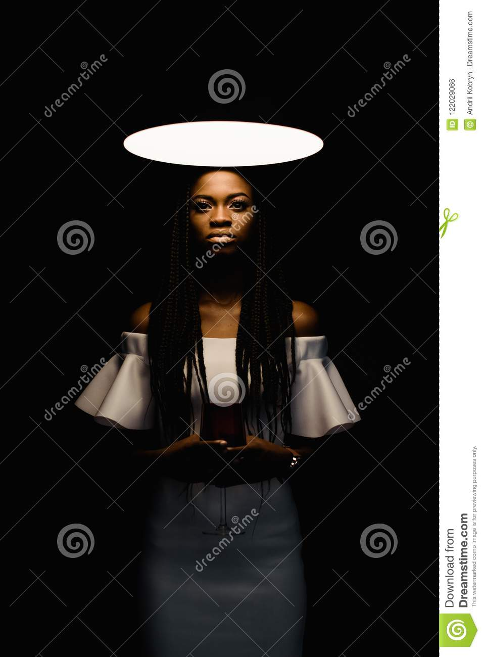 Close up photo of charming, touching, tender, beautiful african woman standing under bright light and looking at the