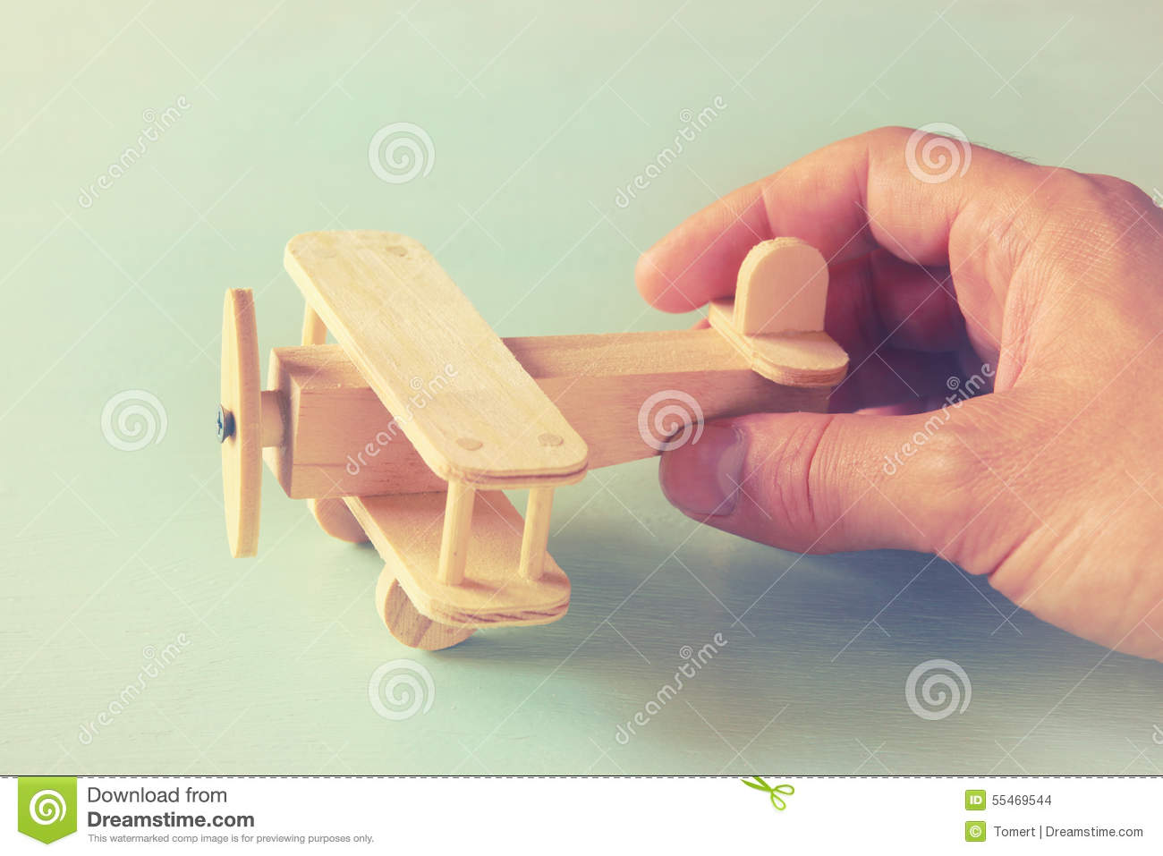 Close up photo of man s hand holding wooden toy airplane over wooden background. filtered image. aspiration and simplicity concept