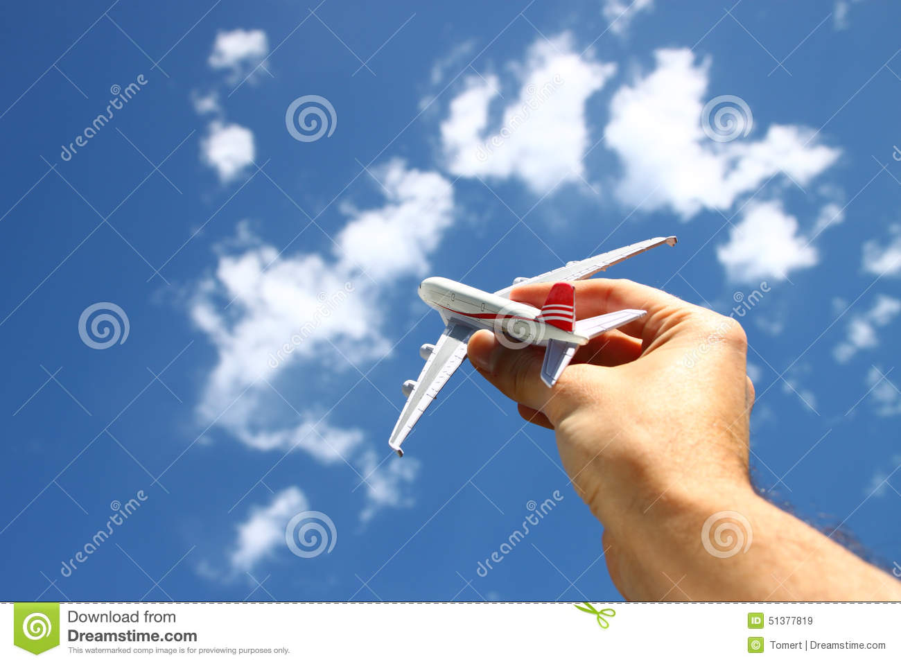 Close up photo of mans hand holding toy airplane against blue sky with clouds. filtered image