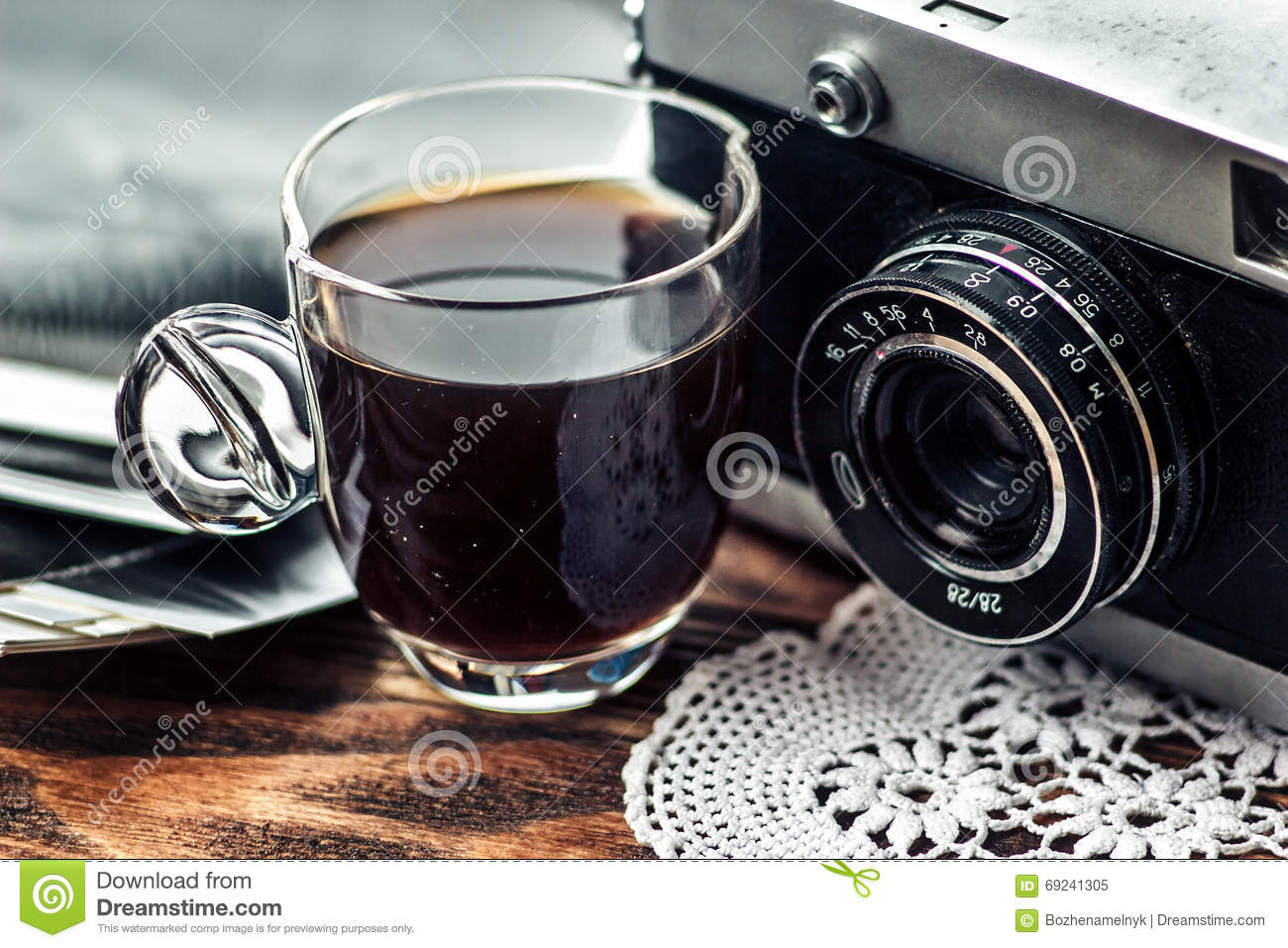 Close up photo of old, vintage camera lens with cap of coffee and black and white photos over wooden table.