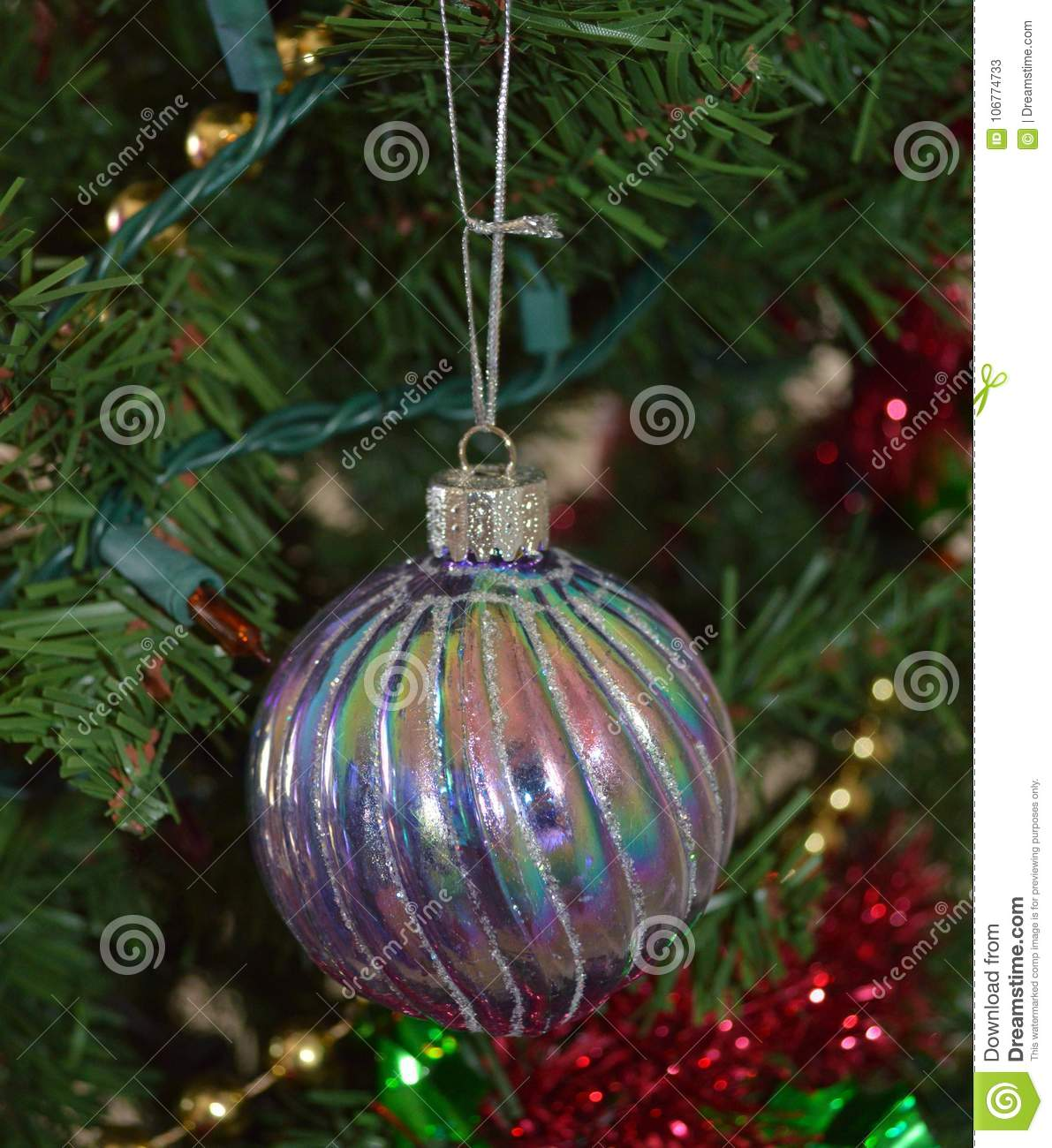 a close up photo of a silver and rainbow glass christmas bulb ornament on a green decorated christmas tree - Glass Christmas Bulbs For Decorating