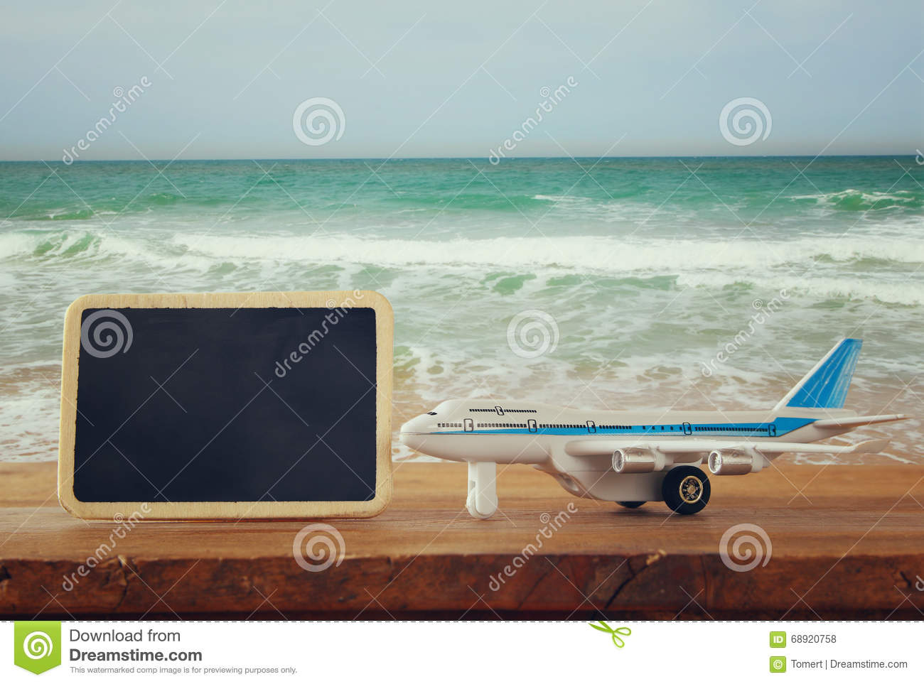 Close up photo of toy airplane next to blank blackboard against sea waves. vintage filtered image, selective focus