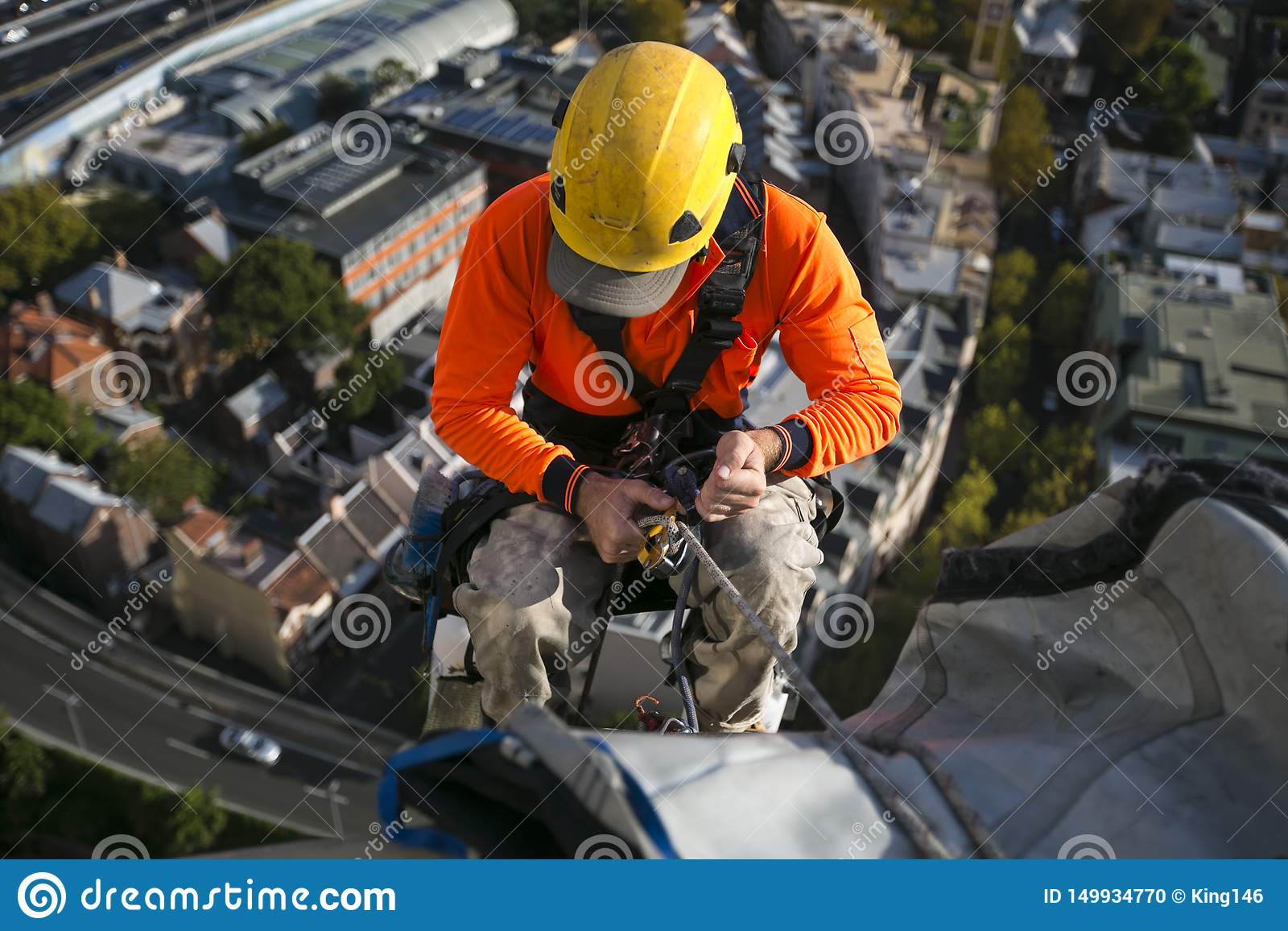 Close up pic of male rope access jobs worker wearing yellow hard hat, long sleeve shirt, safety harness, working at height