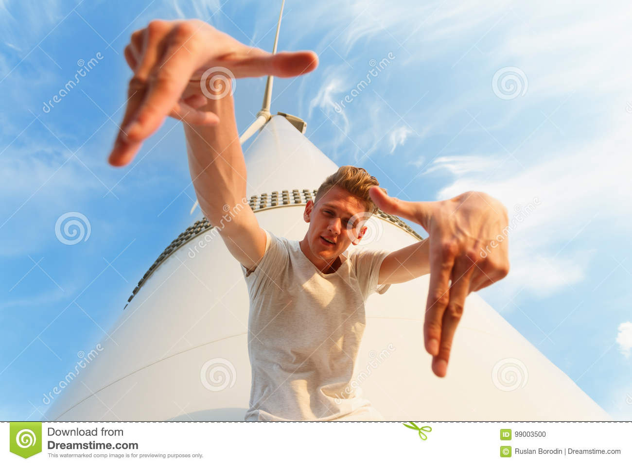 Close-up of a cool teenage guy. A handsome man near the electric windmill. A confident male on a blue sky background.