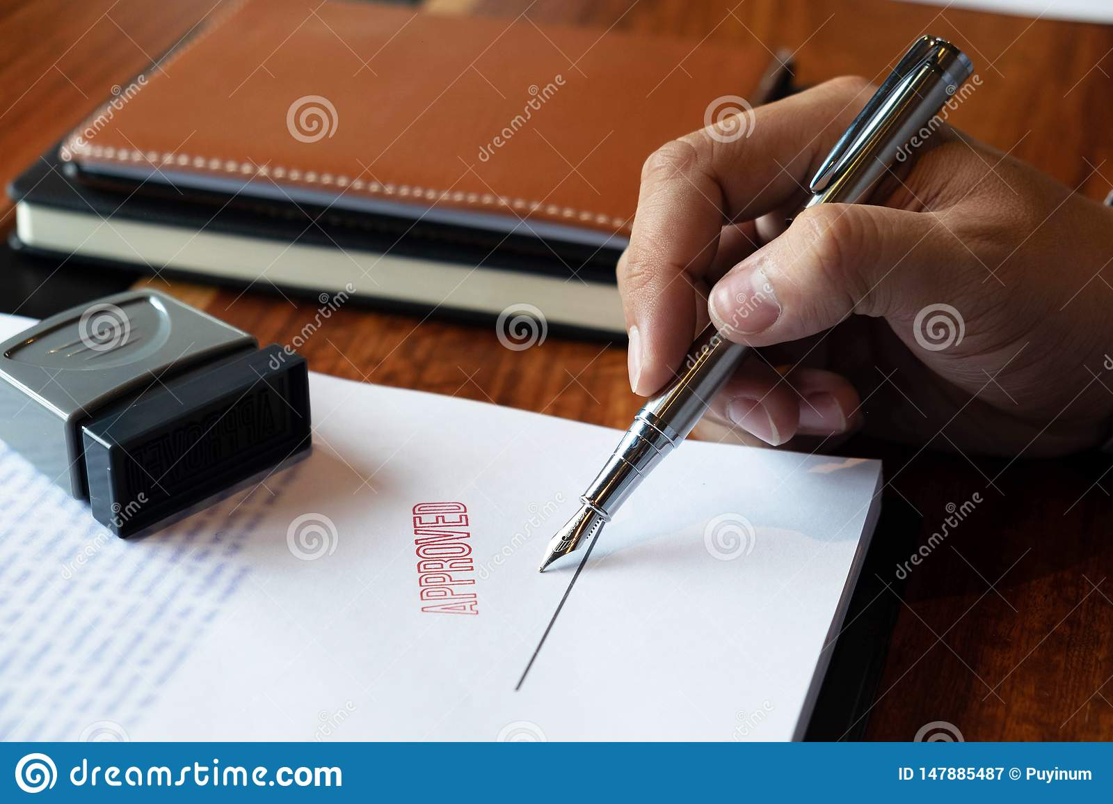 Close-up pictures of the hands of businessmen signing and stamping in approved contract forms