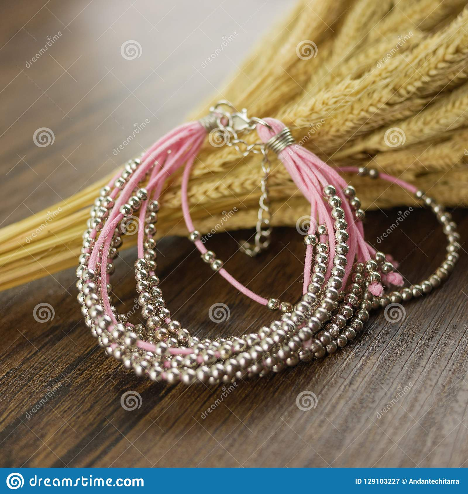 Pink bracelet on wooden background
