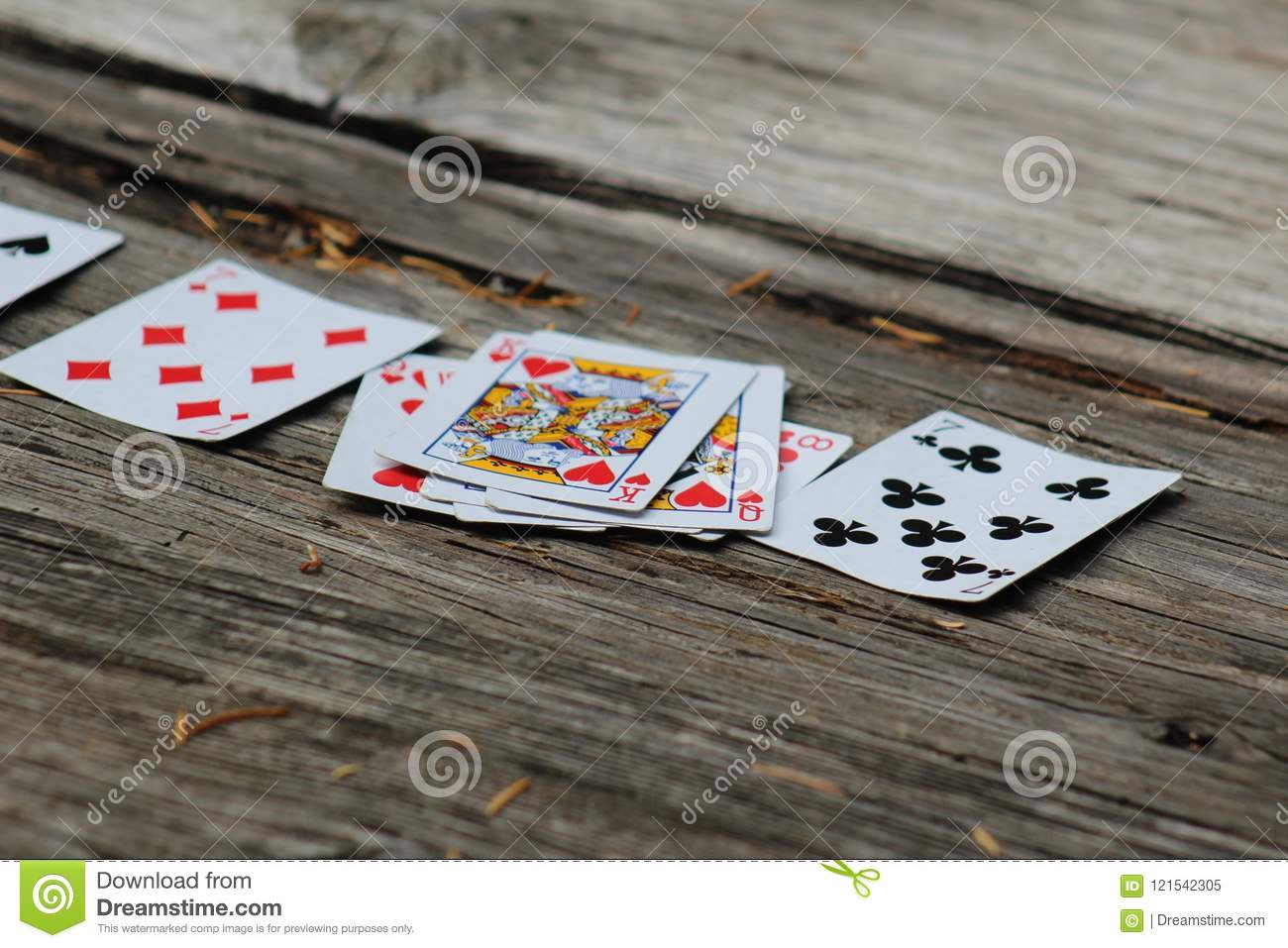 Close-Up of Playing Cards on Old Outdoor Wooden Table