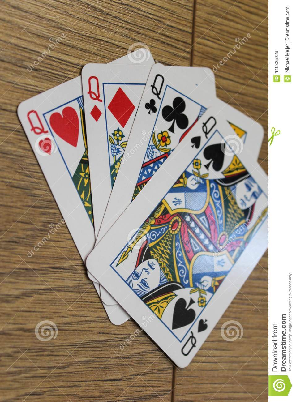 Poker cards on a wooden backround, set of queens of clubs, diamonds, spades, and hearts