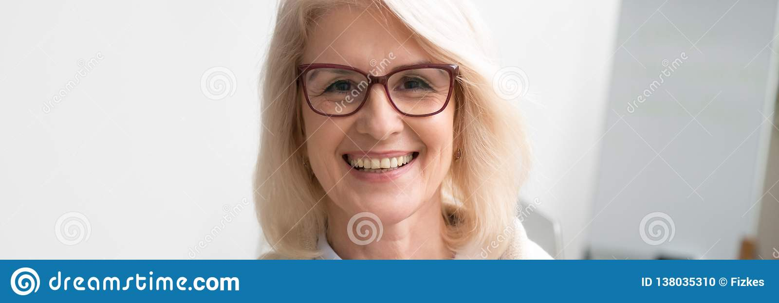 Horizontal image face of aged businesswoman smiling looking at camera