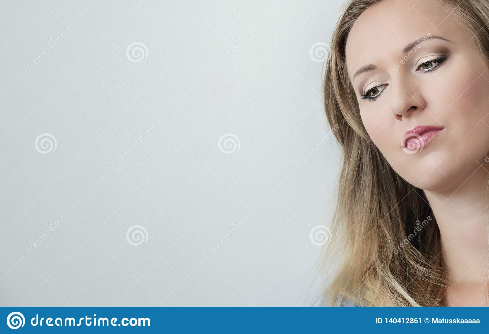 Close-up portrait of attractive young beautiful woman face looking down. Pretty blonde woman with green eyes