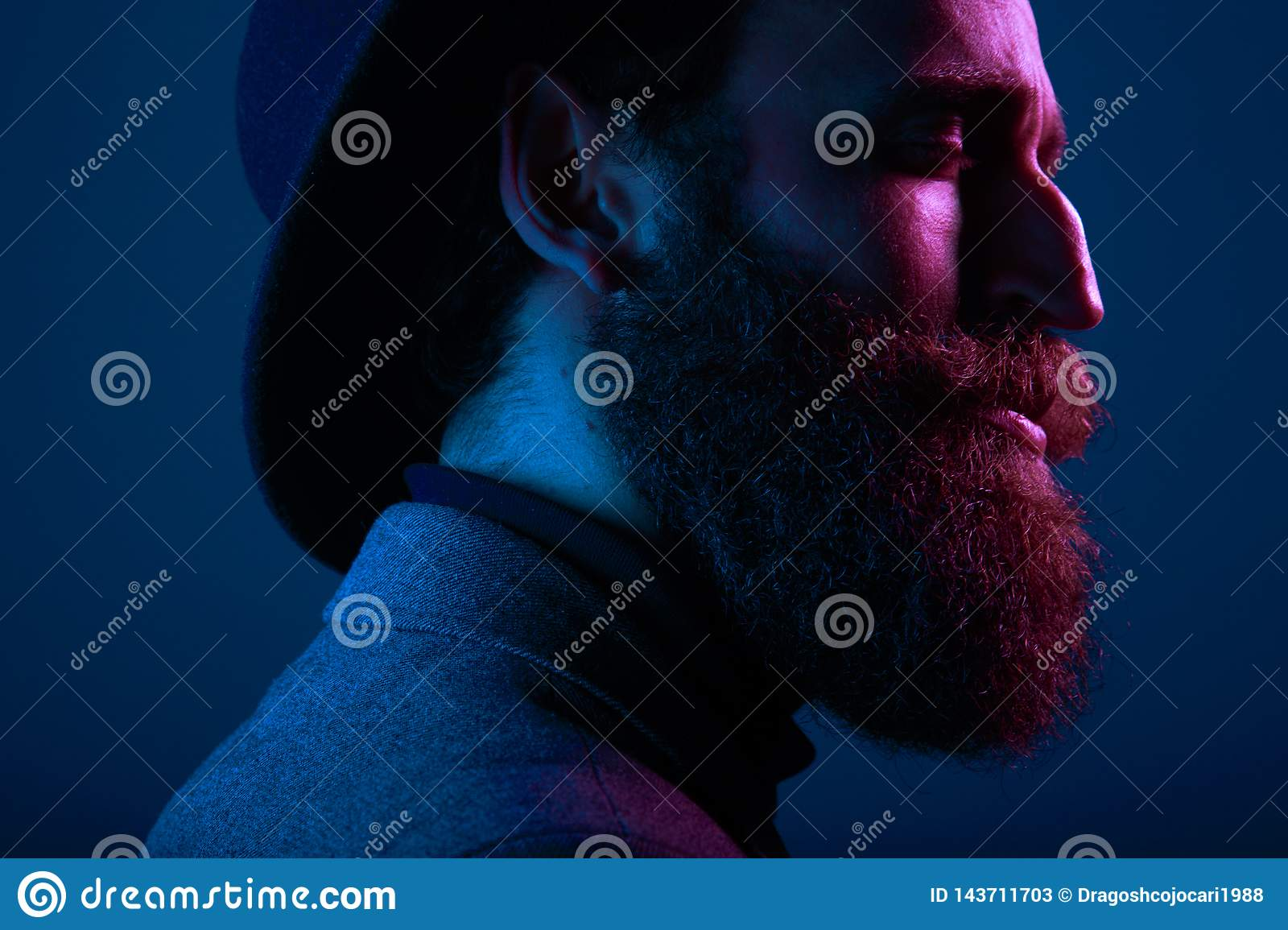 Close up portrait of a bearded man in hat and suit, with close eyes posing in profile, on dark blue background.