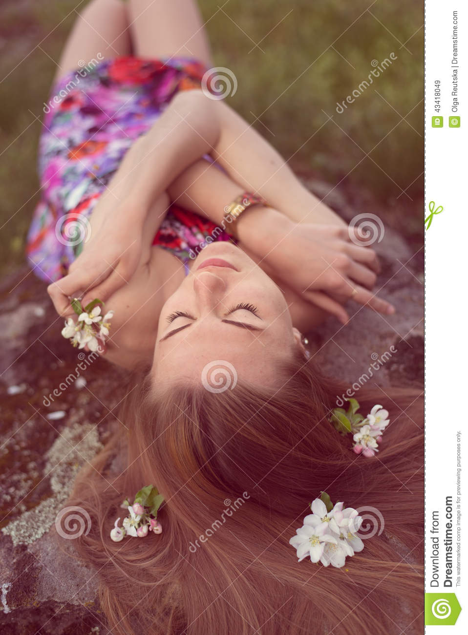 Close up portrait of beautiful blonde young woman laying on stone with flowers in her hair closing eyes dreaming outdoors