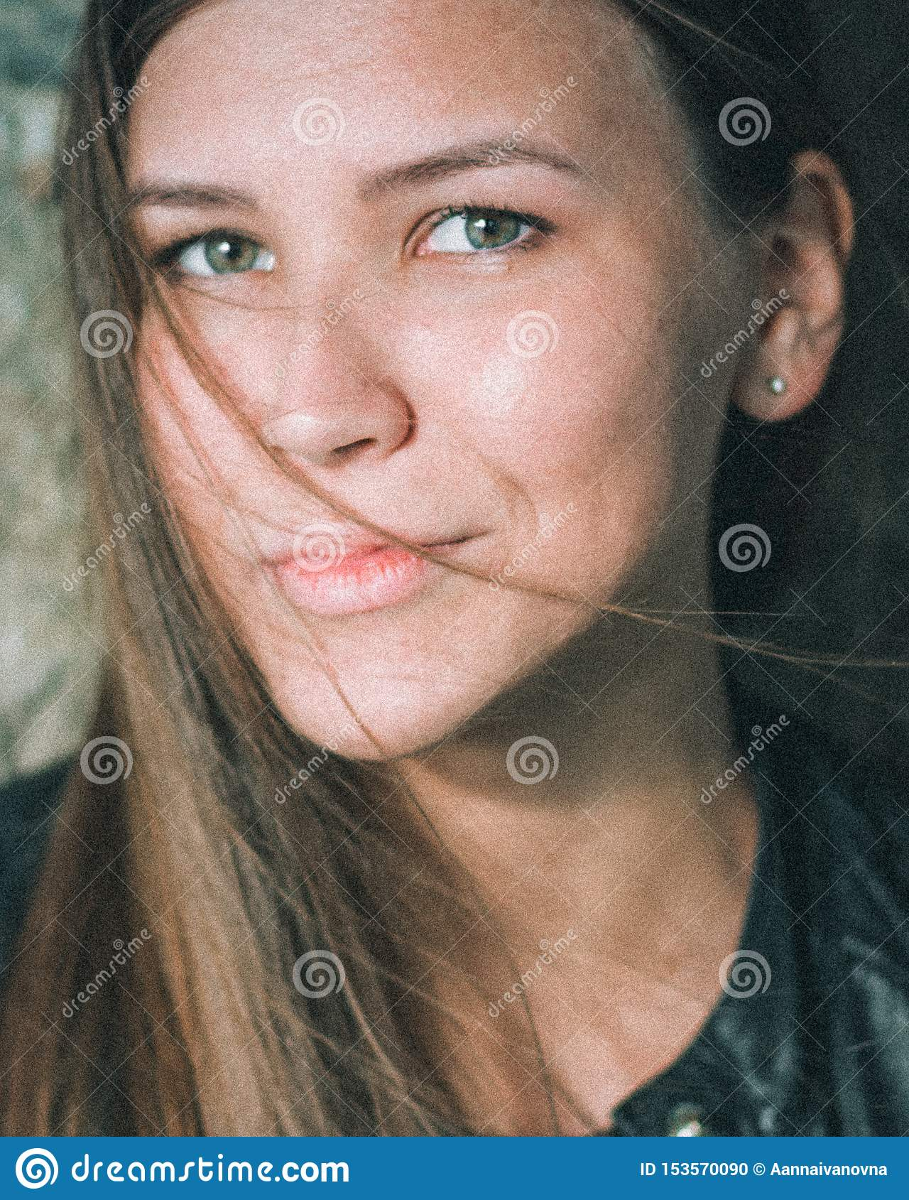 Close-up portrait of a beautiful caucasian girl with long blond flowing hair . A young woman looks straight into the
