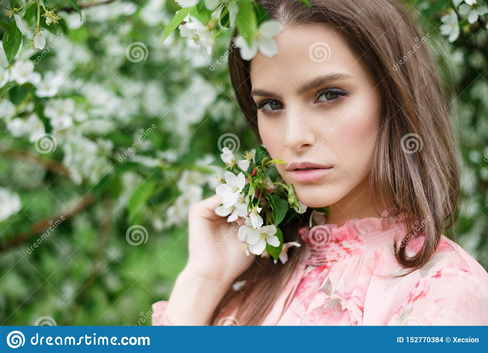 Close-up portrait of a beautiful girl in flowering trees. Flowering fruit trees