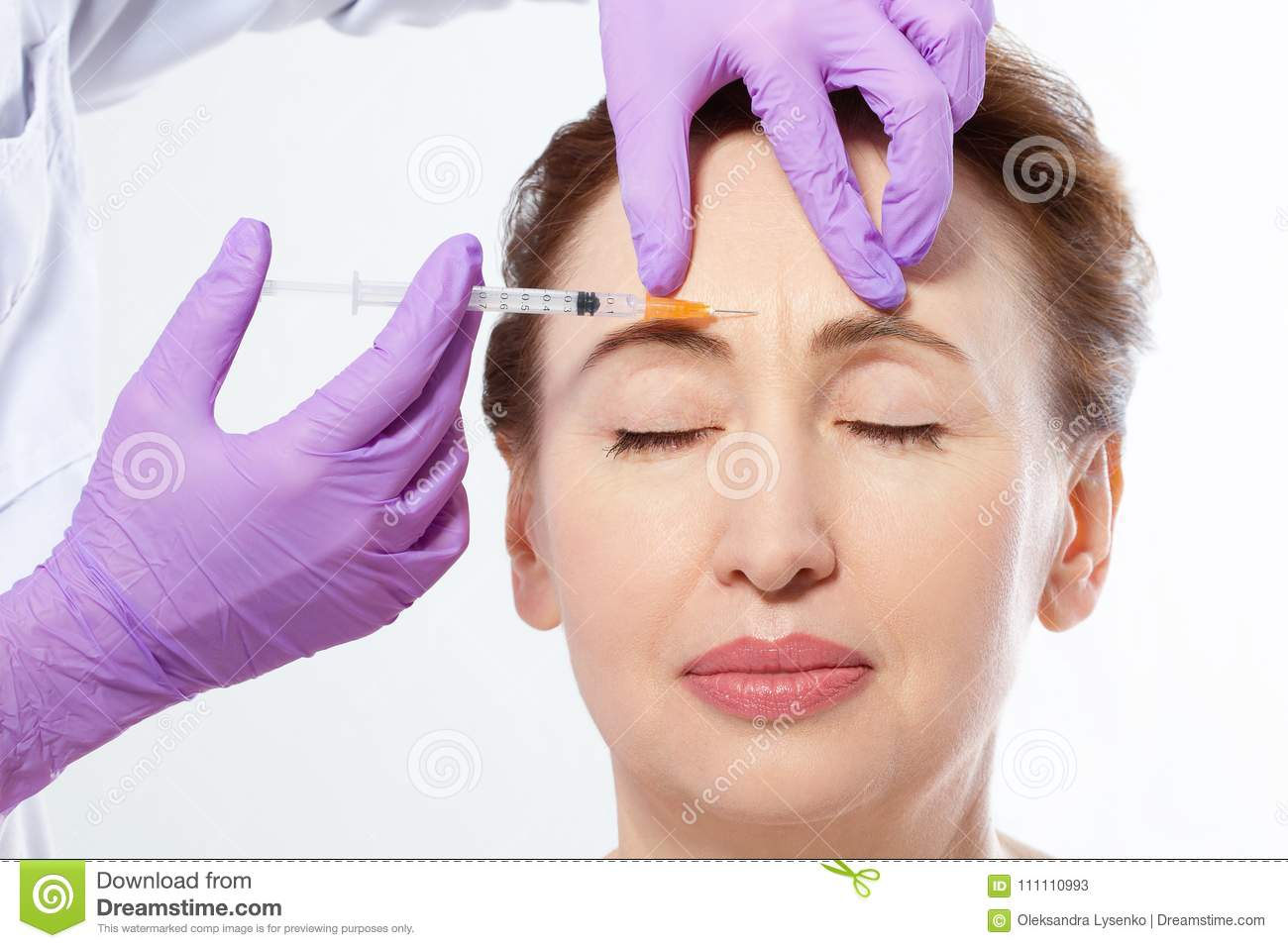 Close-up portrait of a beautiful middle age woman and doctor hands making botox injection isolated on white background. Collagen.