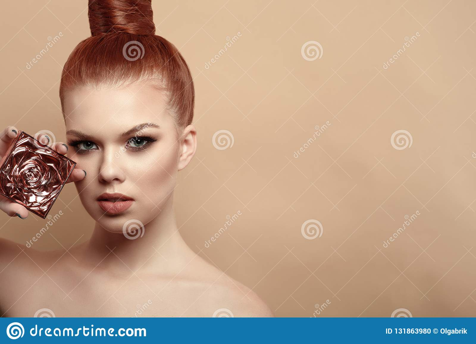Close up portrait of beautiful red-haired woman with perfect make-up and hair scraped back into a high bun holding compact powder
