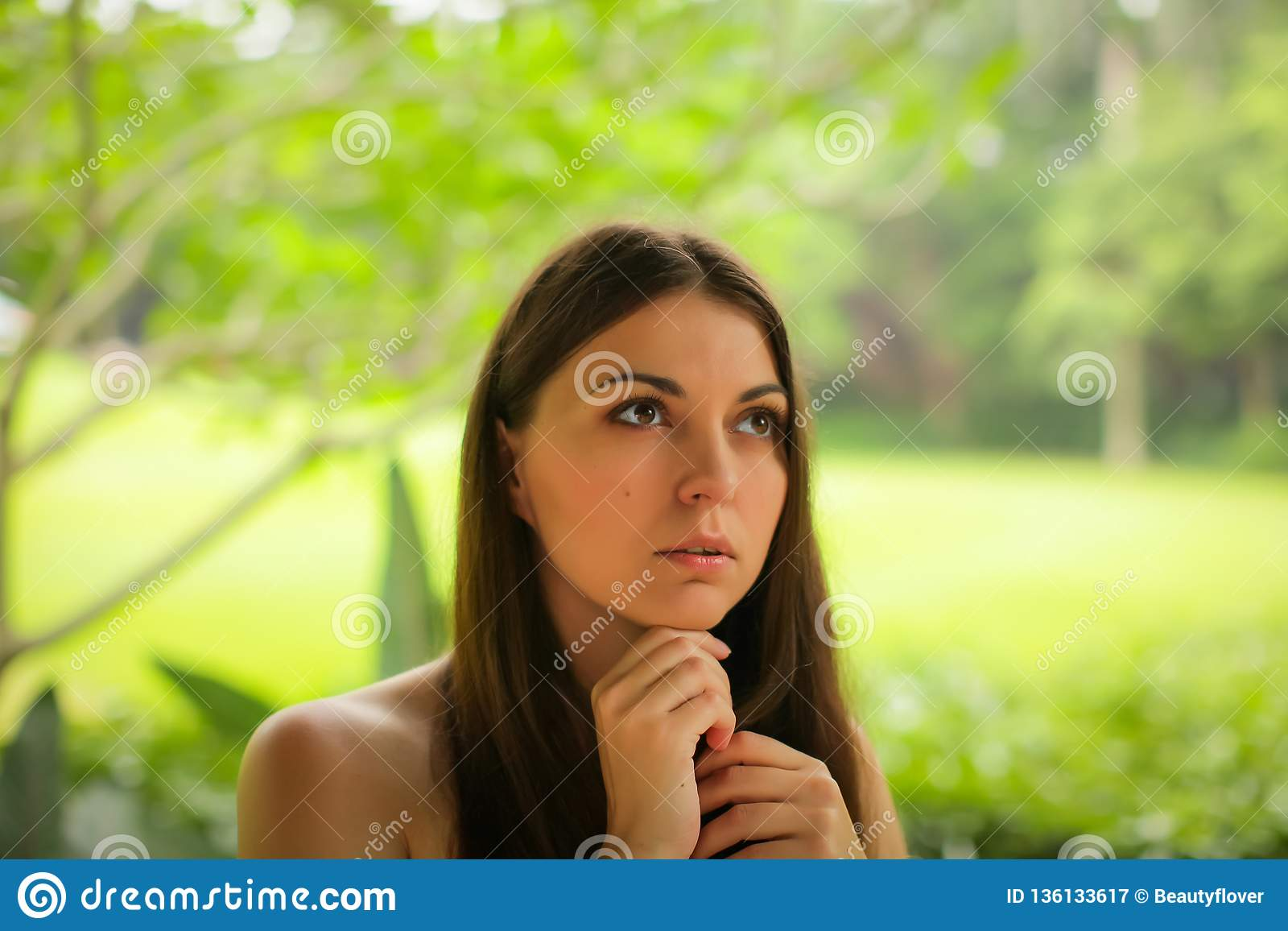 Close up portrait of carefree caucasian young woman posing with different emotions in green summer park