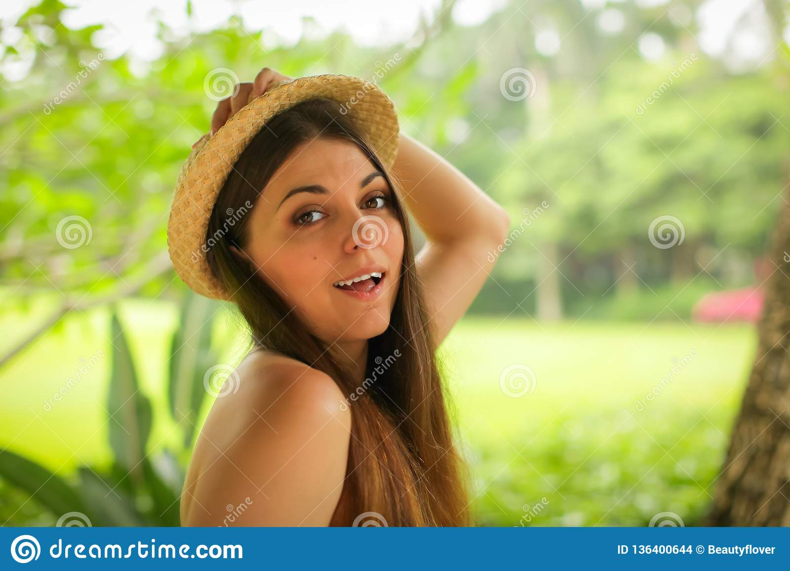 Close up portrait of carefree caucasian young woman with straw hat posing with different emotions in green summer park