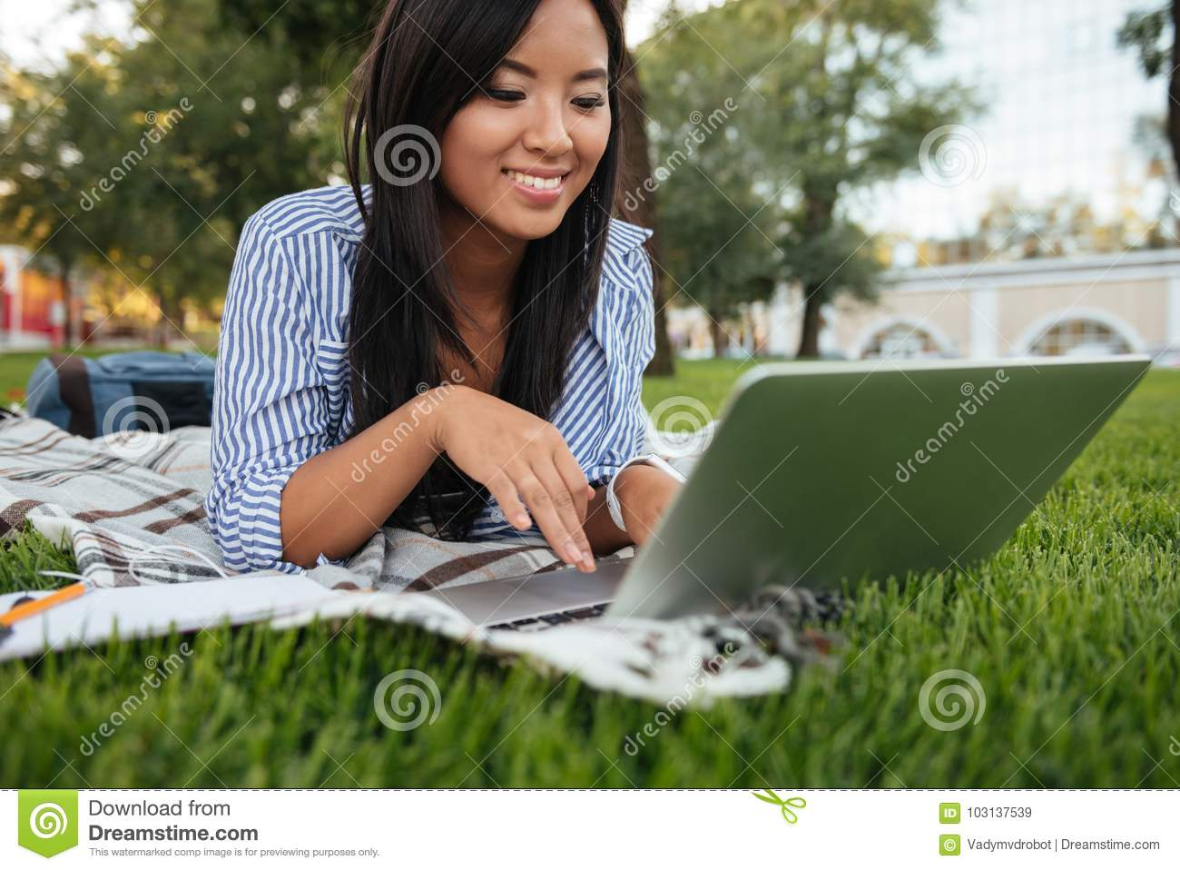Close-up portrait of cheerful asian student, typing on laptop, o