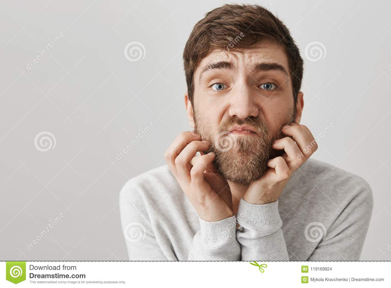 Close-up portrait of clumsy unshaven adult man scratching beard while looking with unsatisfied look at camera as if it