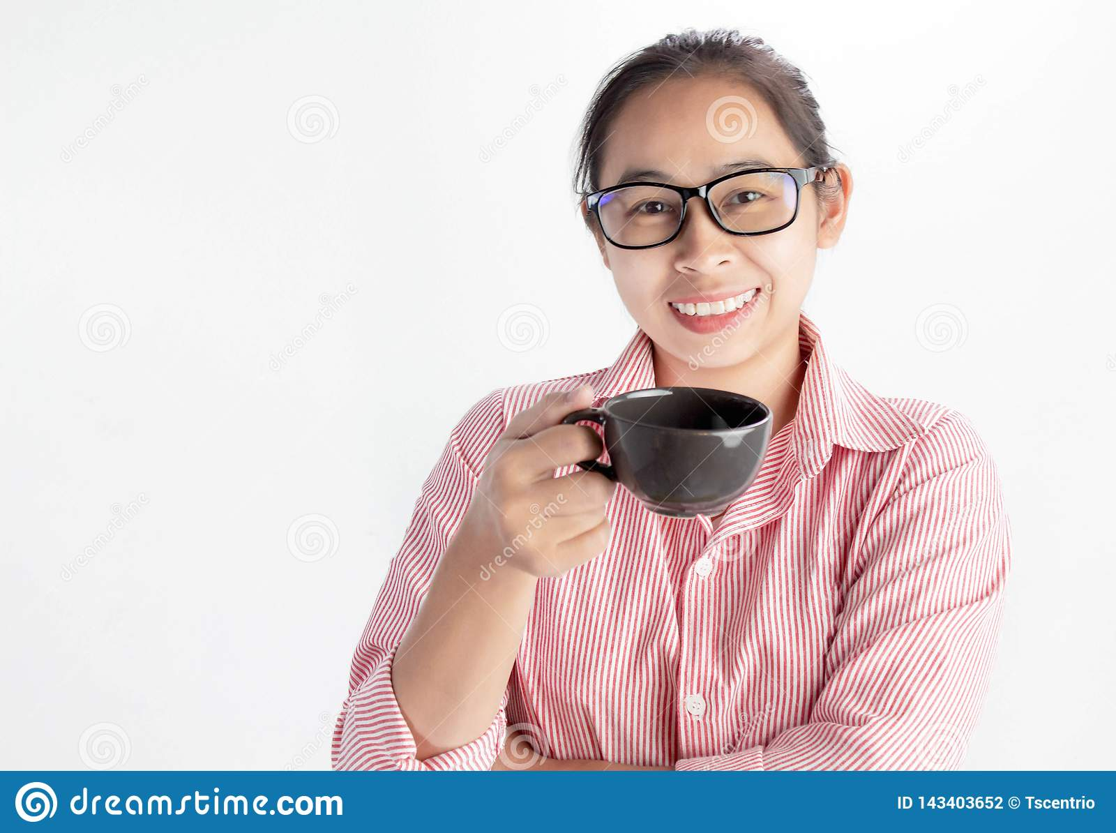 Close up portrait of confident Asian woman, wearing glasses and holding coffee cup, looking camera and smile, standing over white