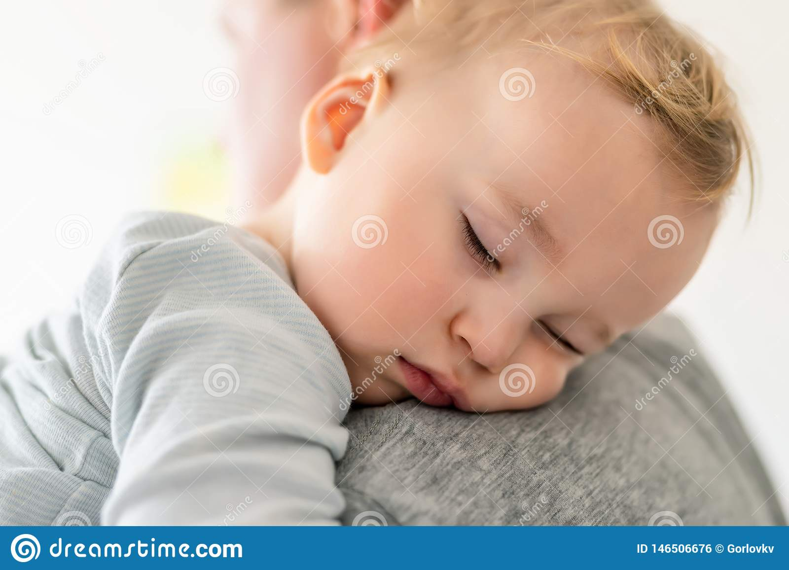 Close-up portrait of cute adorable blond caucasian toddler boy sleeping on fathers shoulder indoors. Sweet little child feeling