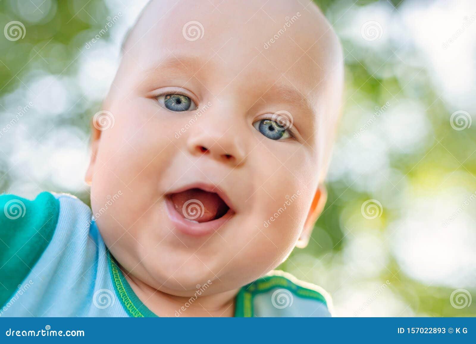 Close-up portrait of cute adorable caucasian blond toddler boy having fun in park or garden outdoors. Close selfie portrait of