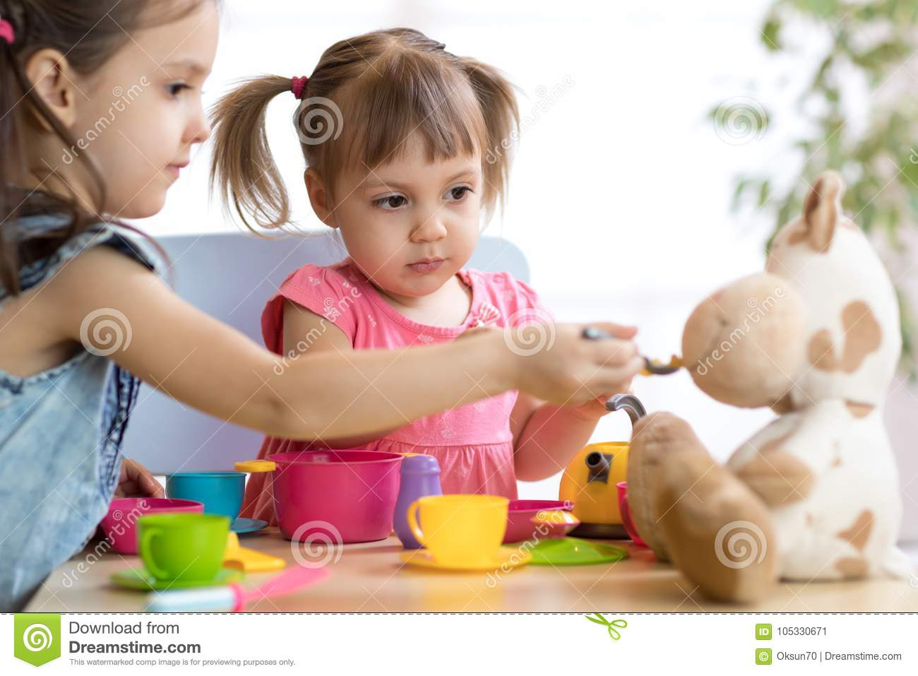 Close-up portrait of cute adorable little kids feeding caw plush toy