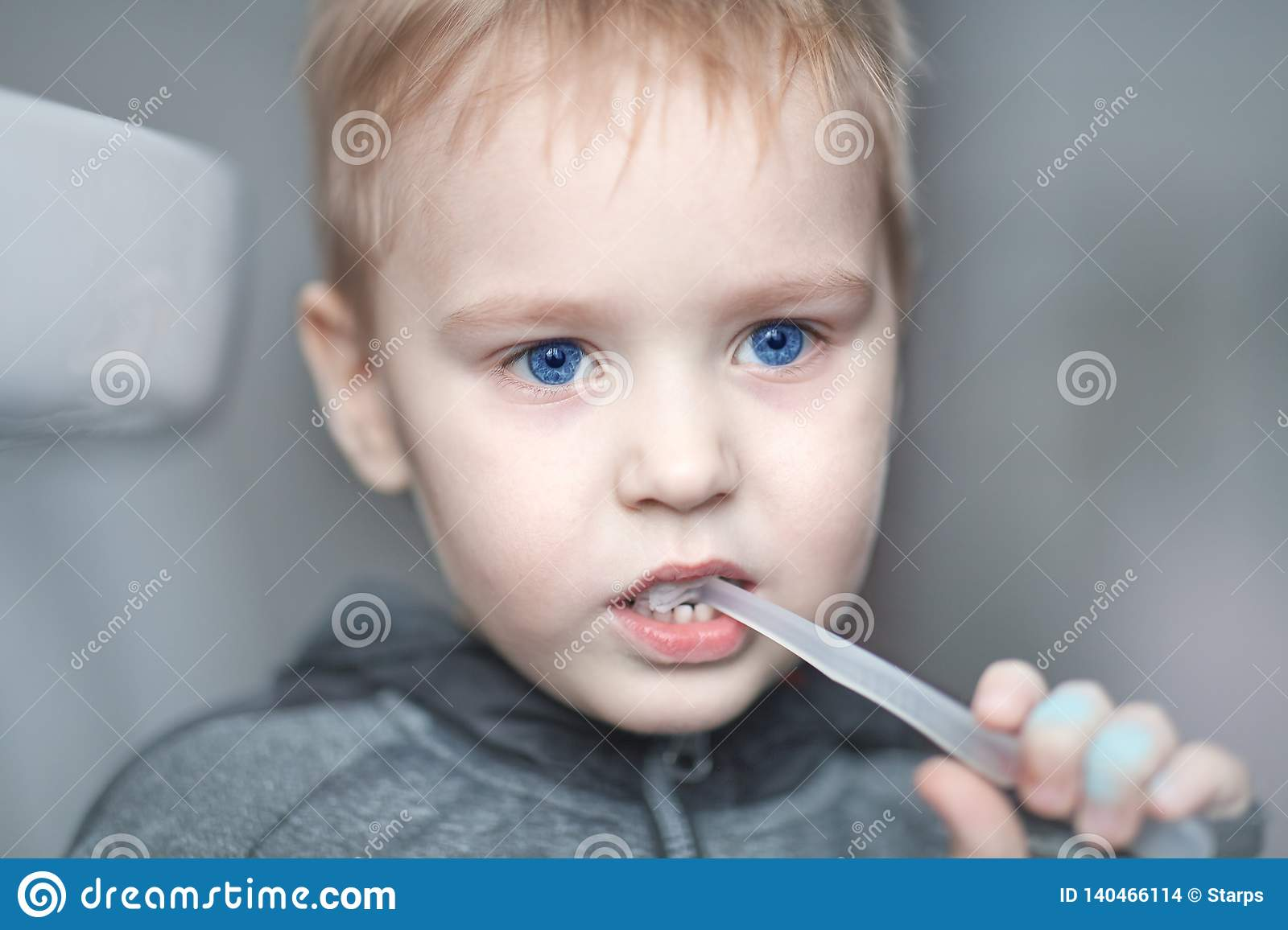 Close up portrait of cute caucasian baby boy with very serious face expression cleaning the teeth with teeth brush, by himself. Br