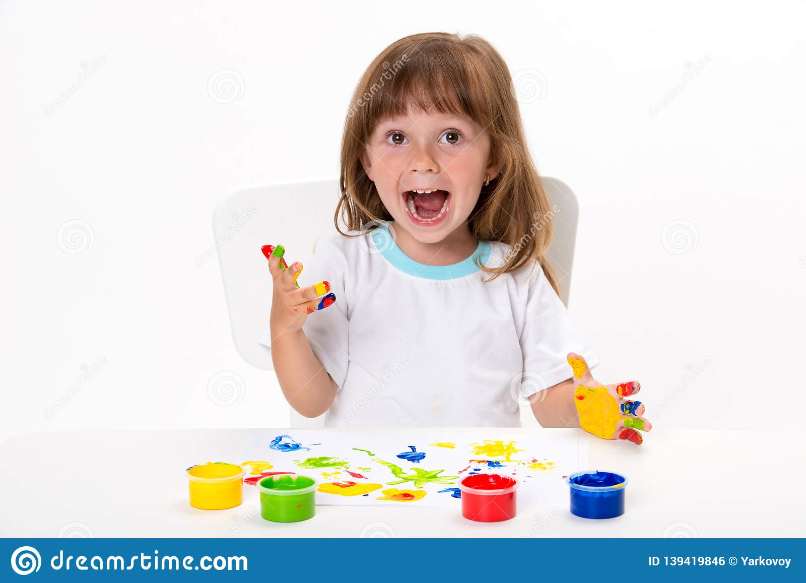 Close-up portrait of a cute cheerful happy smiling little girl draws her own hands with gouache or finger paints isolated on white