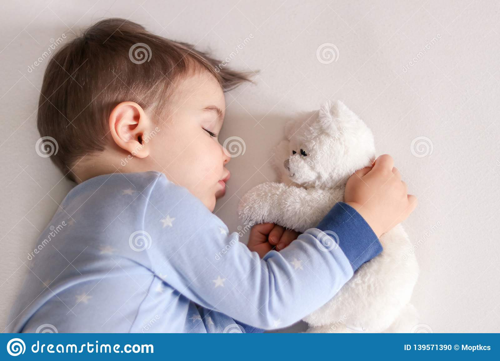 Close up portrait of cute little baby boy in light blue pajamas sleeping peacefully on bed at home hugging white soft teddy bear t